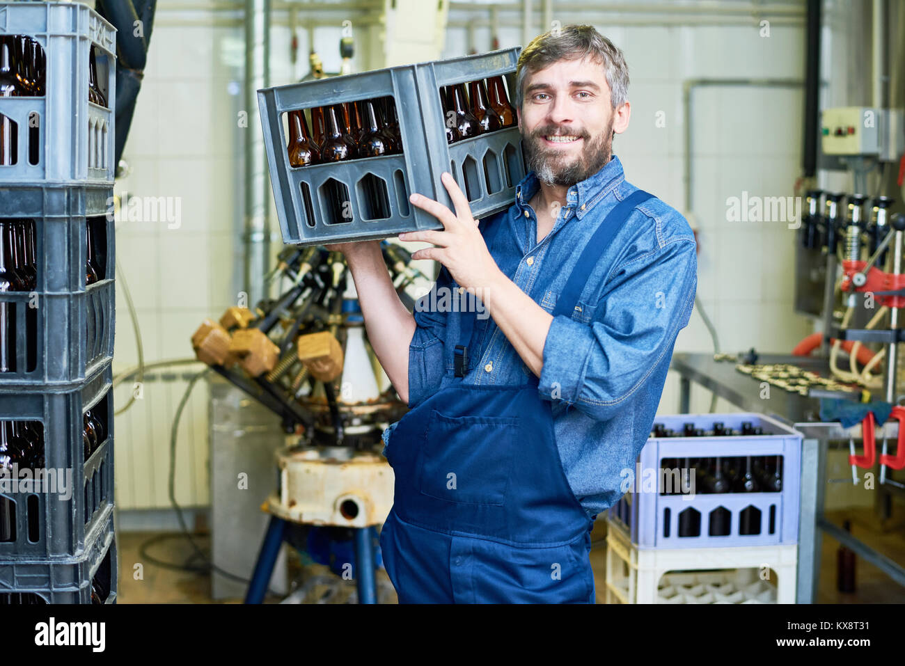 Bearded Worker Carrying Beer Bottle Crate - Stock Image