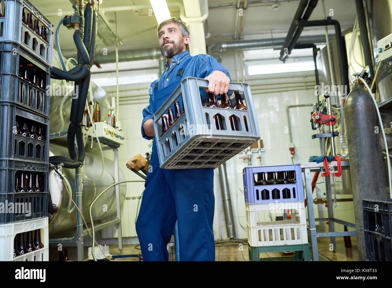 Brewing Plant Worker Carrying Crate - Stock Image