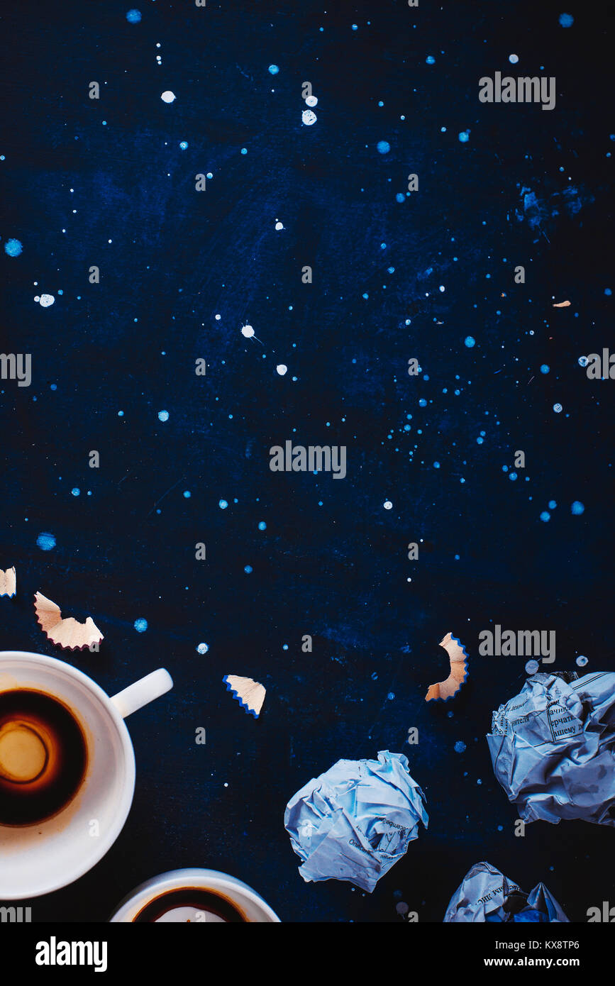 Dark background with crumpled paper balls, empty coffee cups, pencils, paper, notes and notepads. Still life with - Stock Image