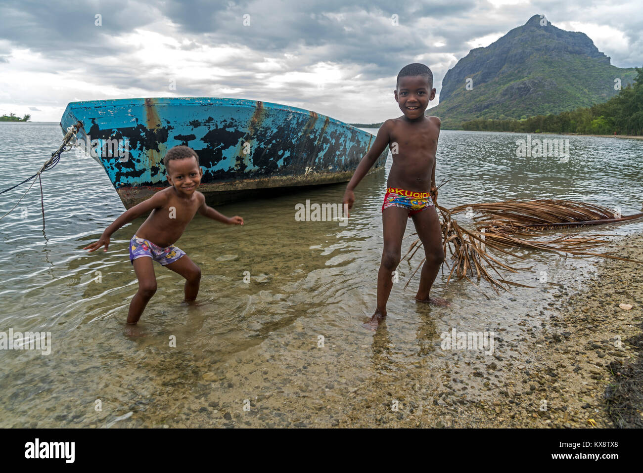 spielende Kinder vor dem Berg Le Morne Brabant, Black River, Mauritius, Afrika  | kids playing at the beach, Le - Stock Image