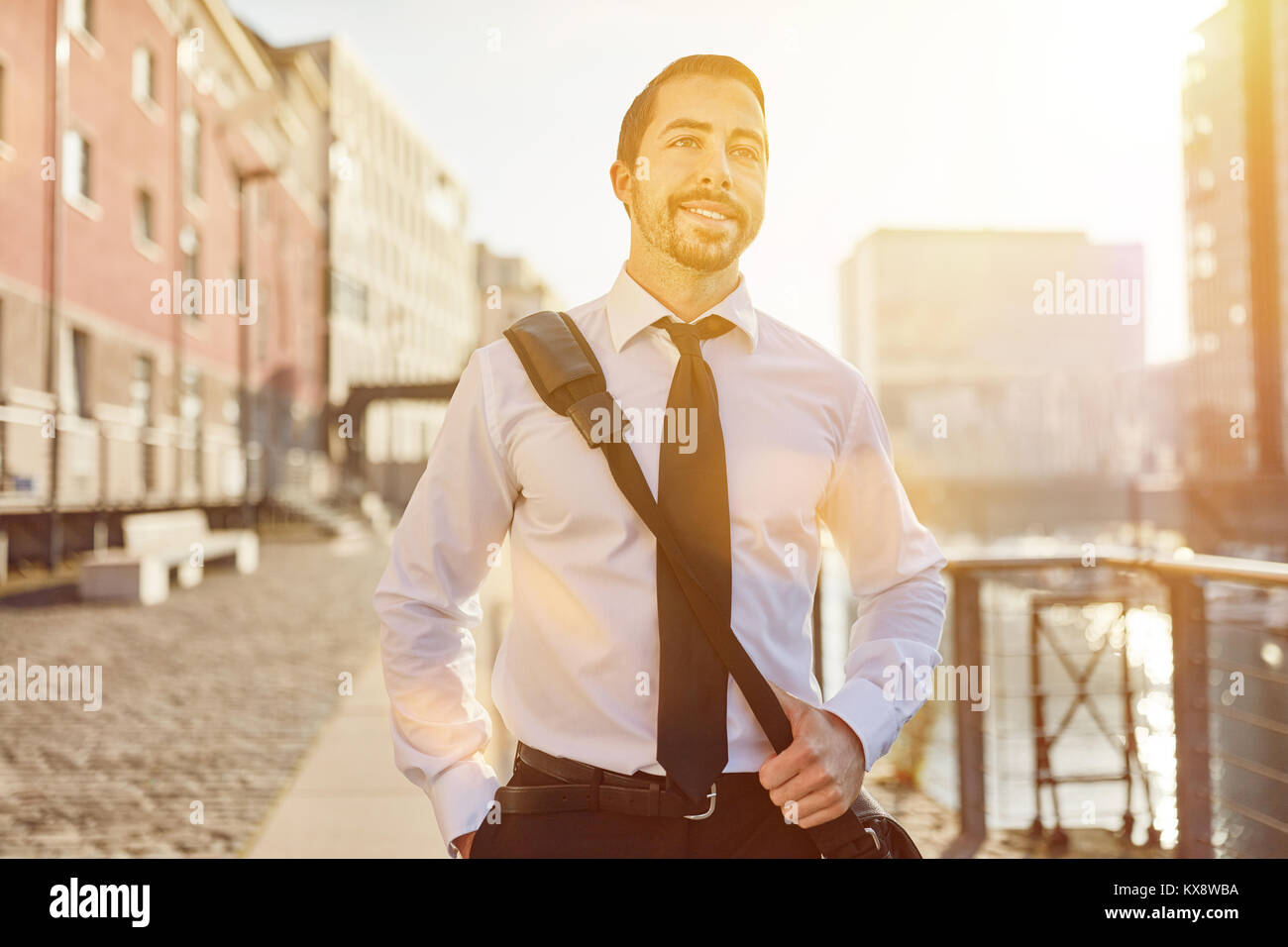 Relaxed business man on the way home smiles relaxed - Stock Image