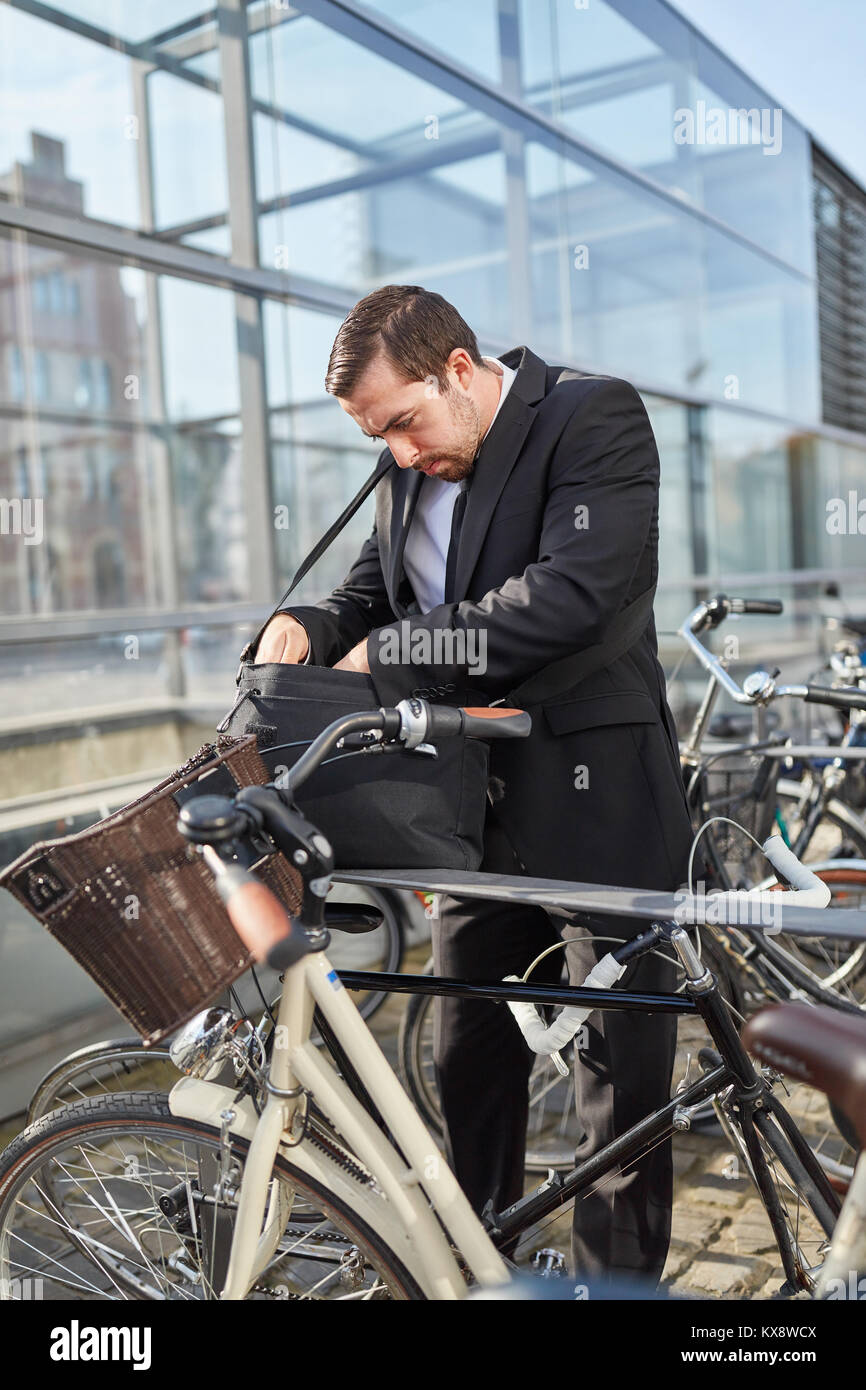 Business man as a commuter looks for the bicycle key - Stock Image