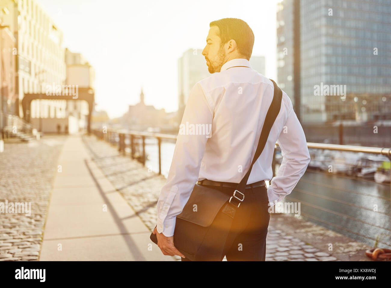Business man as commuter on the way home in summer - Stock Image