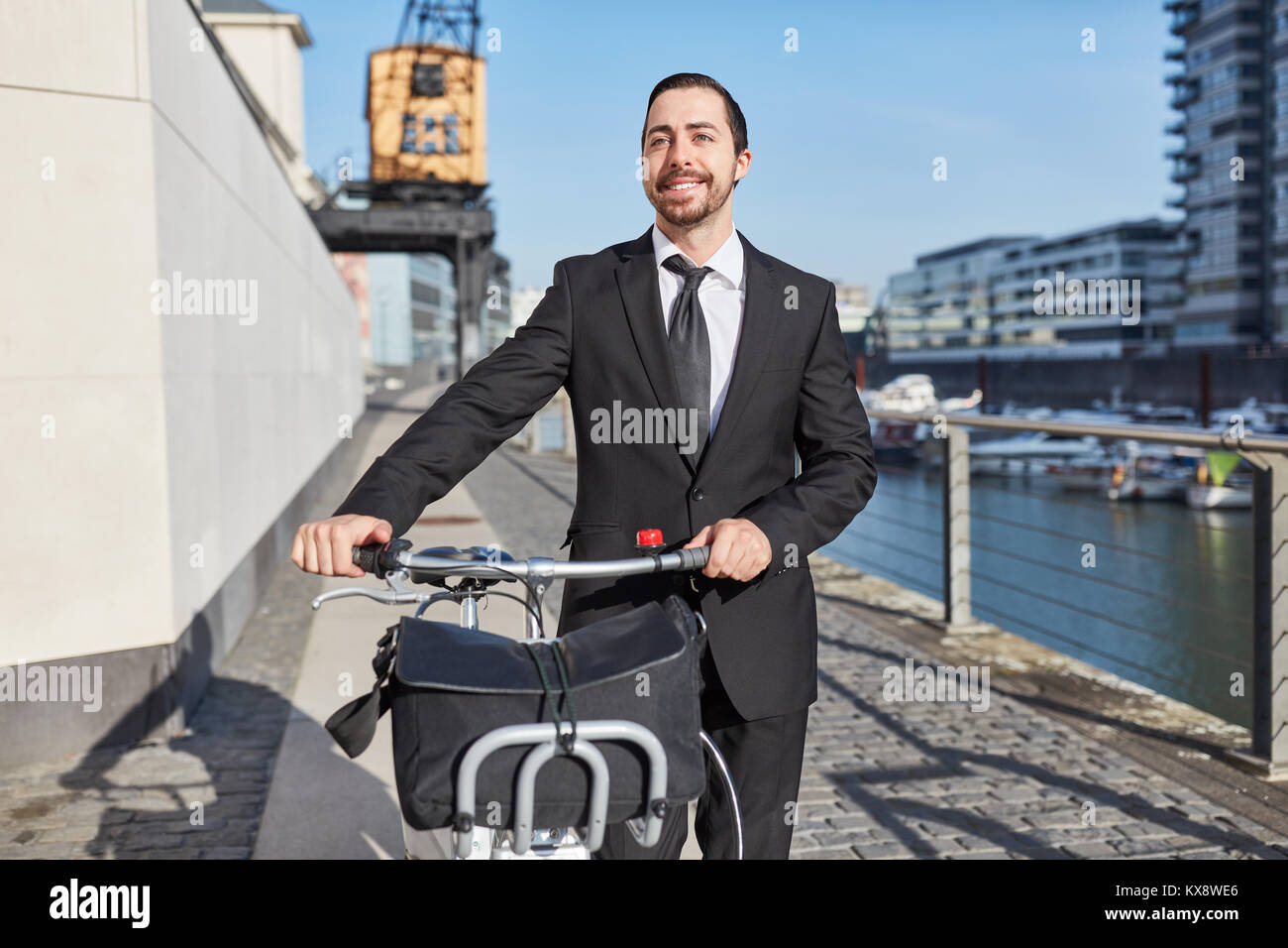 Eco-friendly startup entrepreneur pushes a bike through the city - Stock Image