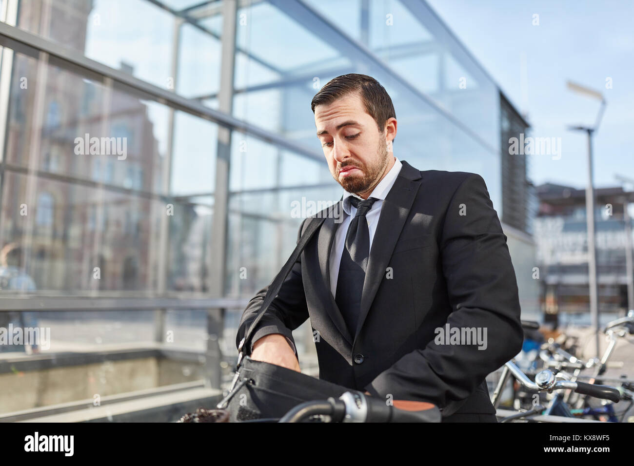 Businessman as a commuter looks frustrated for the bicycle key - Stock Image