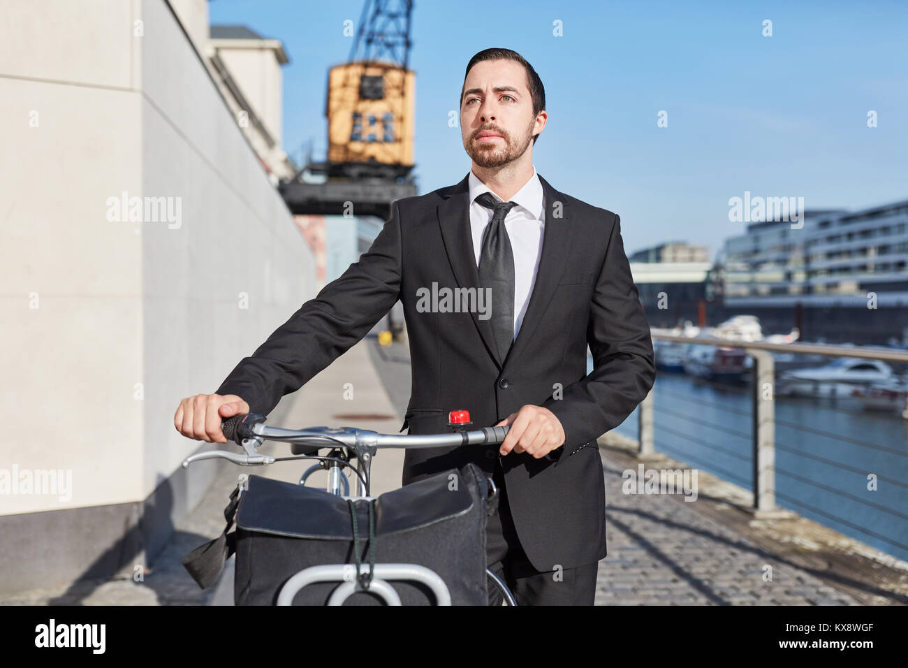 Alternative business founder pushes bicycle through the city - Stock Image