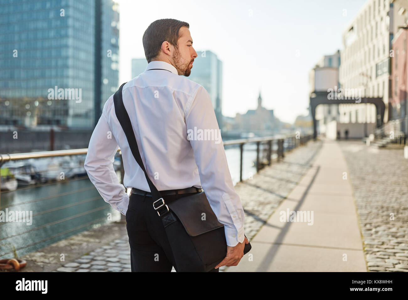 Businessman as commuter walks home through the city - Stock Image