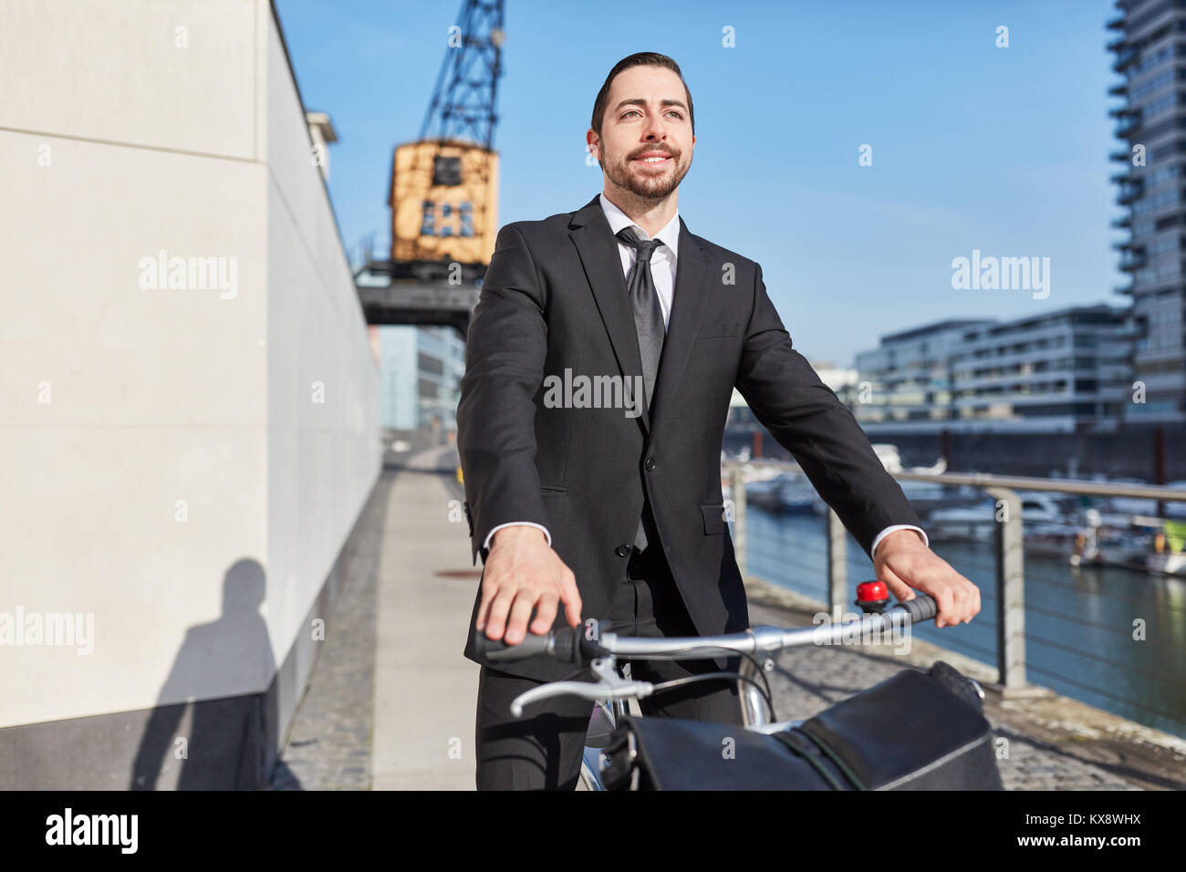 Young entrepreneur with the bike actively on the road in the city - Stock Image