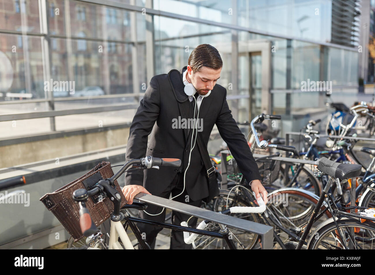 Man as a commuter in front of his bike at the bike rack - Stock Image