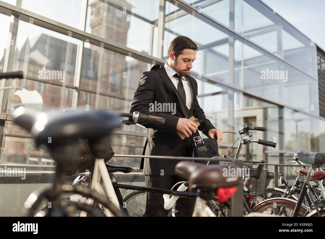 Businessman as a commuter is looking for the key for his bike - Stock Image