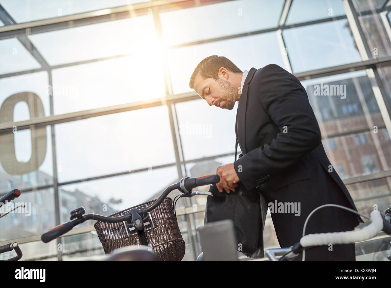 Businessman as commuter and cyclist looks for the bicycle key - Stock Image