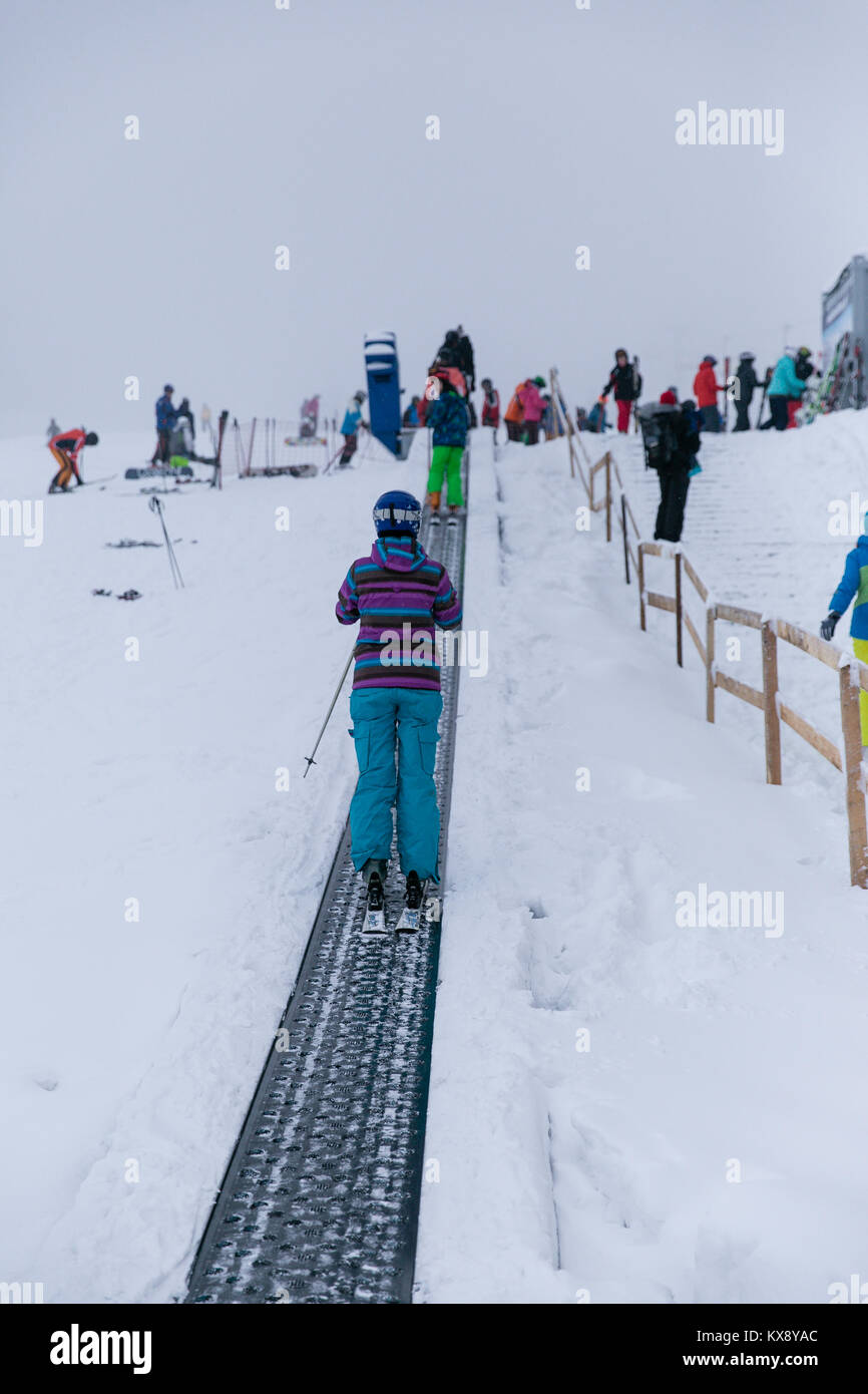 Skier on a tape ski lift on the way to the second leg of chairlift bringing tourists to the summit of Skrzyczne - Stock Image