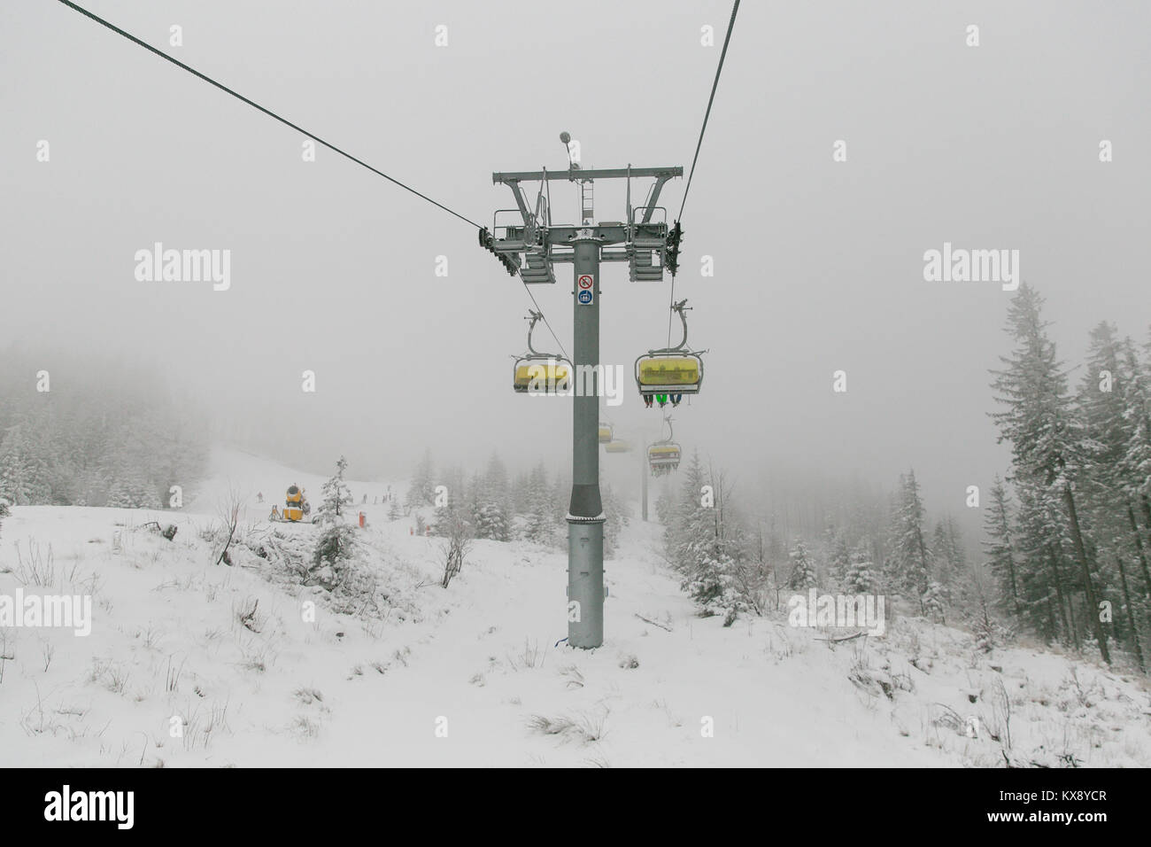 Ski chairlift bringing skiers and snowboarders up the Skrzyczne mountain after heavy snowfall on a misty winter - Stock Image