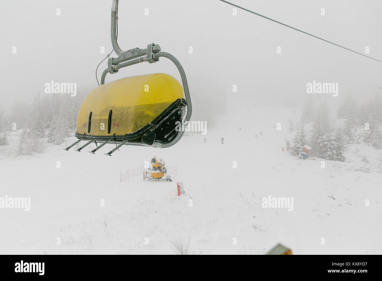 Ski chairlift bringing skiers and snowboarders up the Skrzyczne mountain after heavy snowfall on a misty winter Stock Photo