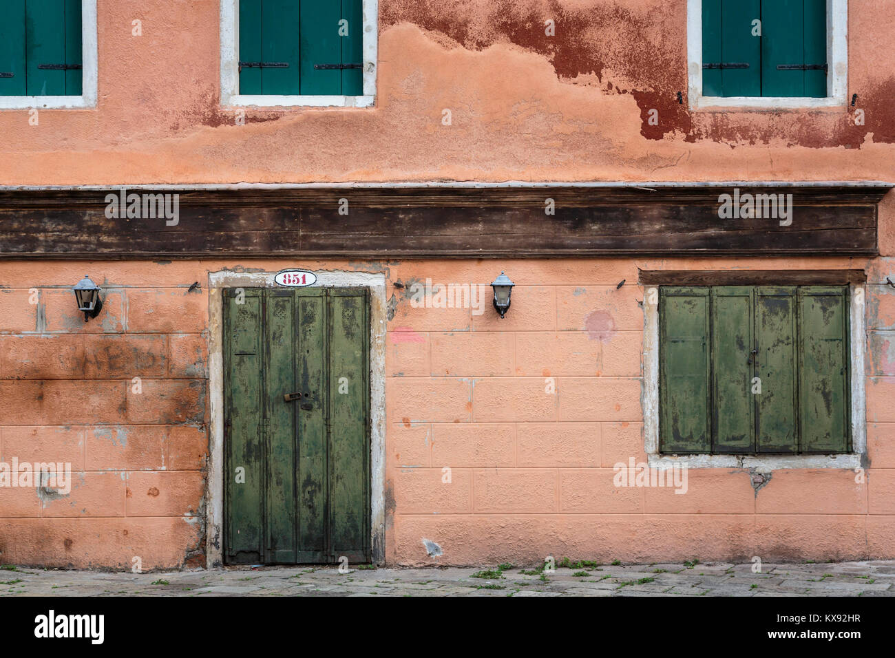 Building door and shuttered windows along a small canal in Veneto, Venice, Italy, Europe. - Stock Image