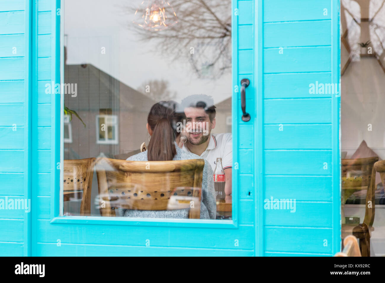 Looking through blue door of young couple conversing - Stock Image