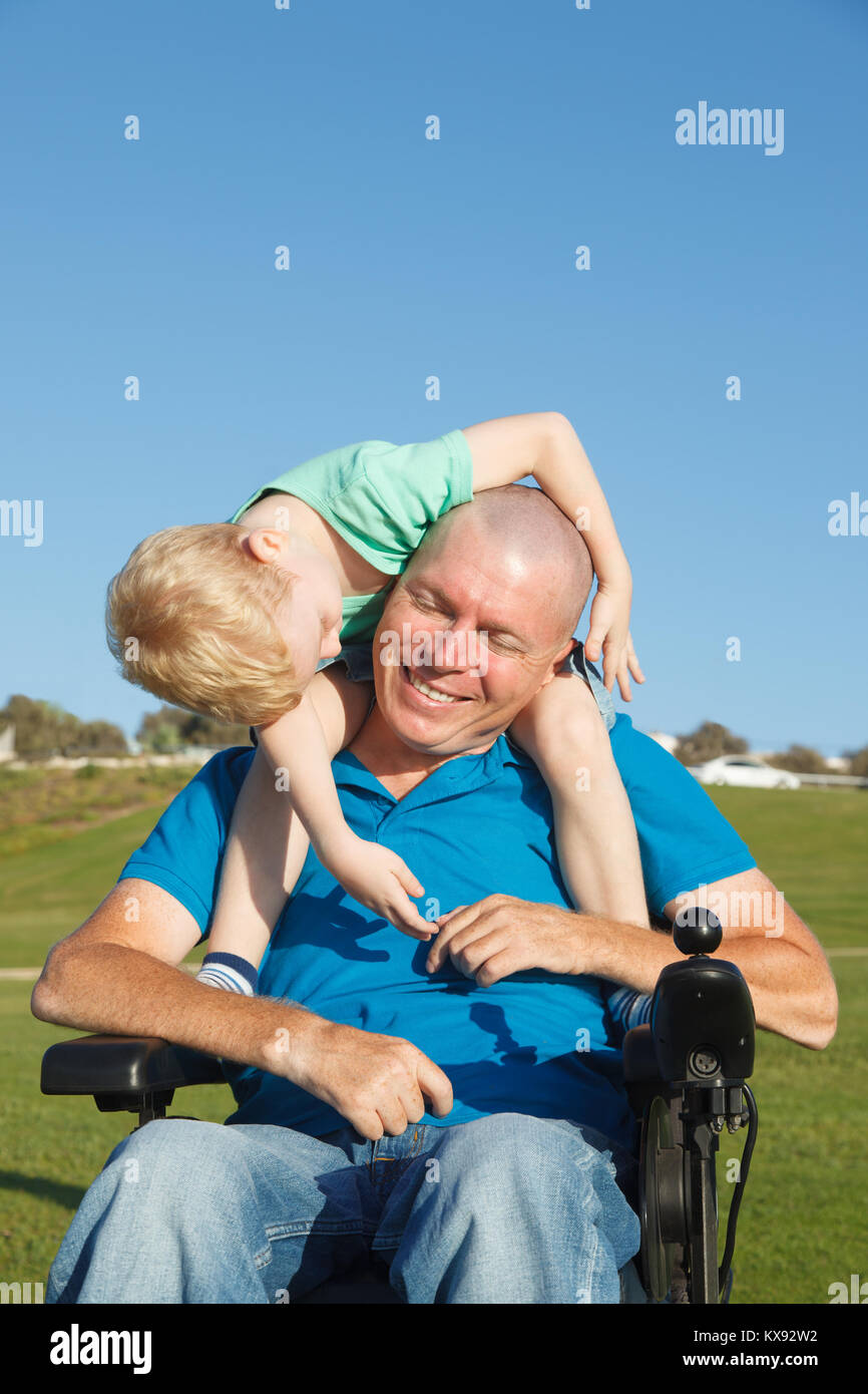 Disabled father giving little son piggyback ride - Stock Image