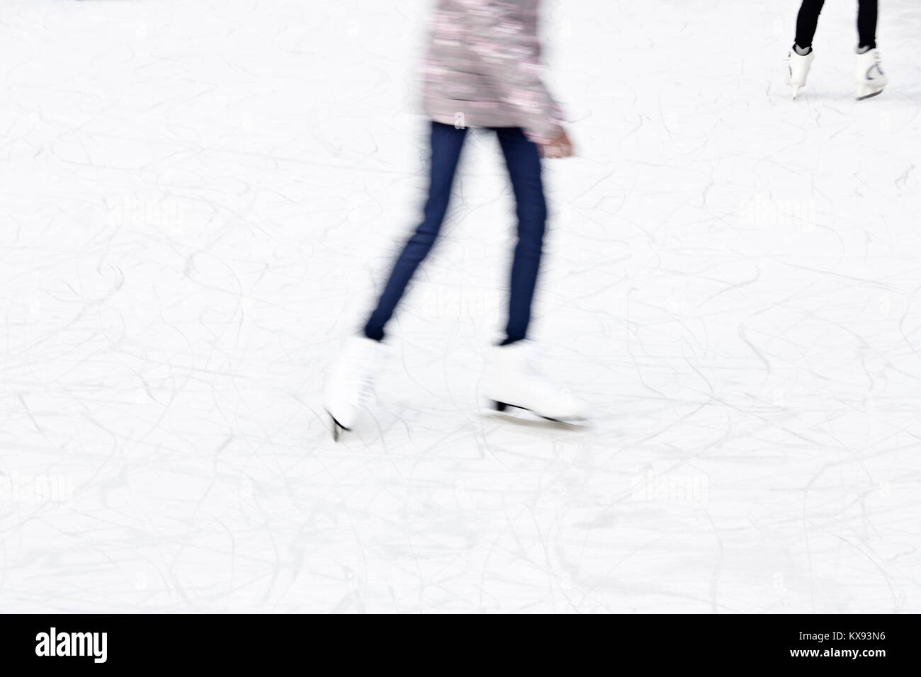 Arty blurry two teenage girl ice skating legs , fun and winter recreation detail - Stock Image