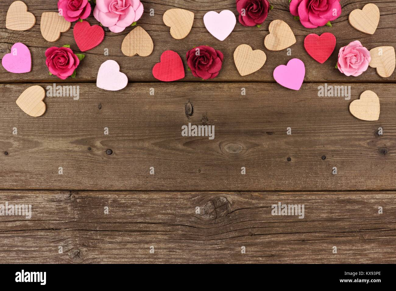 Valentines Day top border of wooden hearts and paper roses against a rustic wood background with copy space. - Stock Image