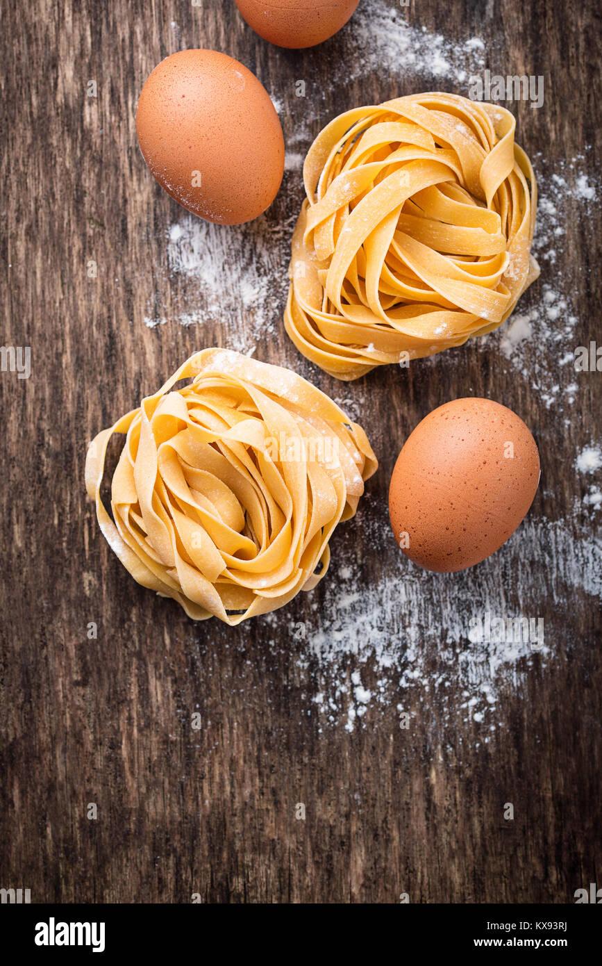 Raw pasta tagliatelle and eggs - Stock Image