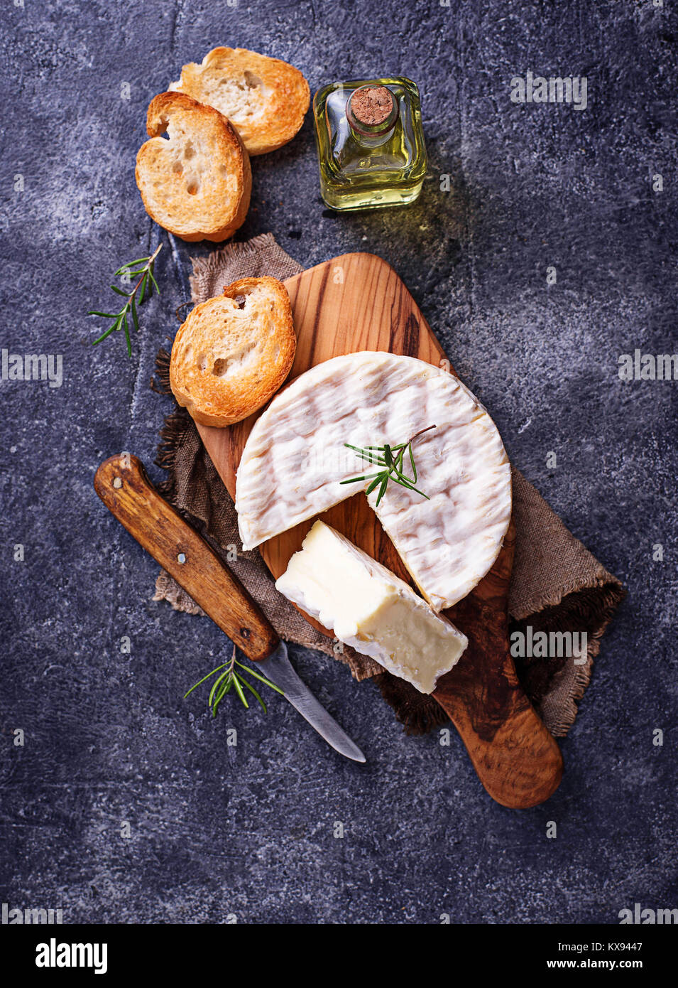 Camembert cheese with rosemary on wooden board - Stock Image