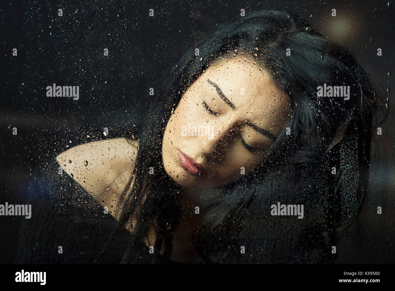 Unhappy depressed sad Woman eyes closed  tearful hand in hair sitting at rainy window  closeup cinematic portrait - Stock Image