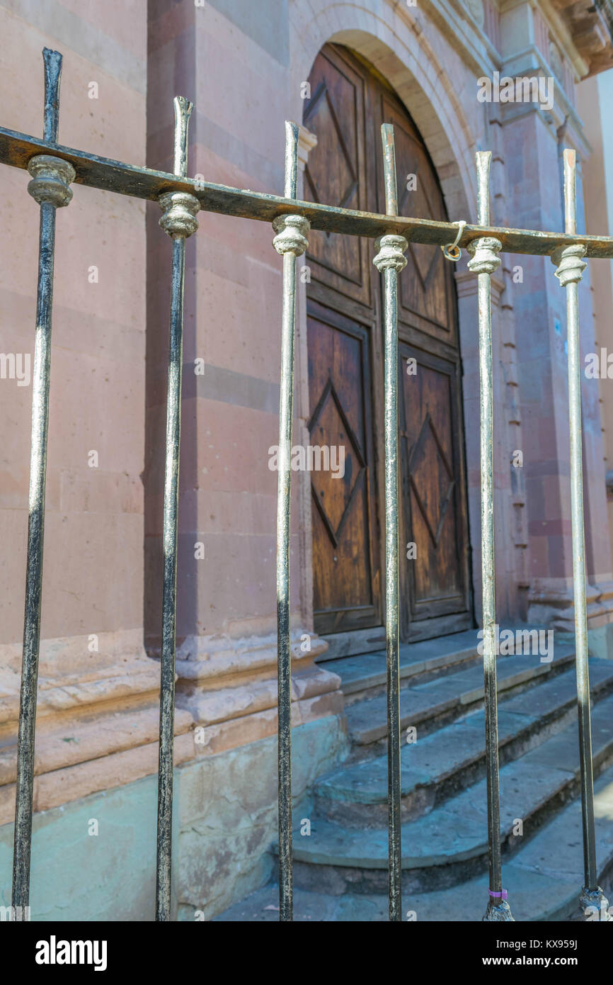 Close-up of an aged iron fence, an old stone building, with stone steps and beautifully carved, arched double wooden - Stock Image