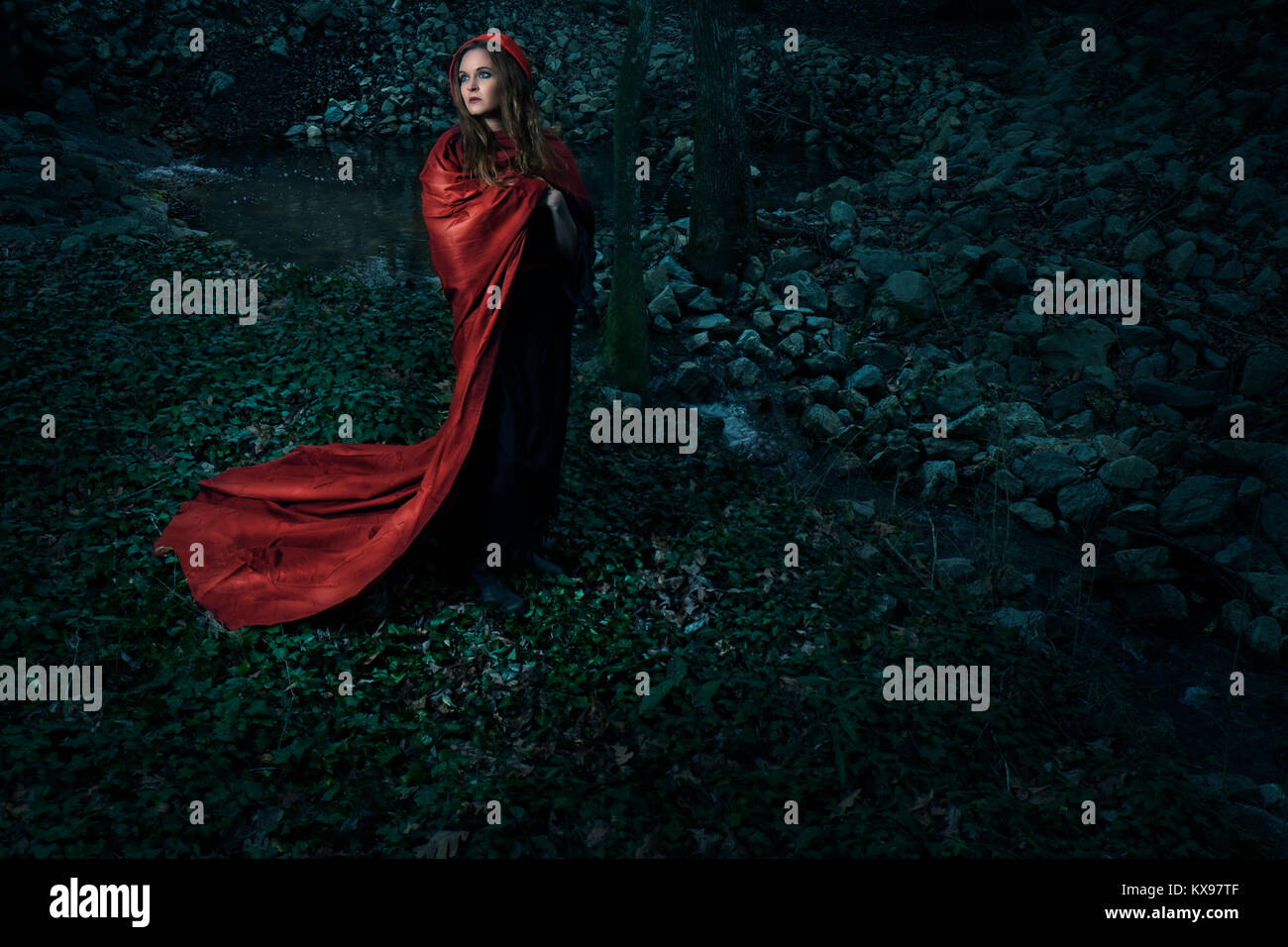 Young woman wrapped in red cape and hood Stock Photo