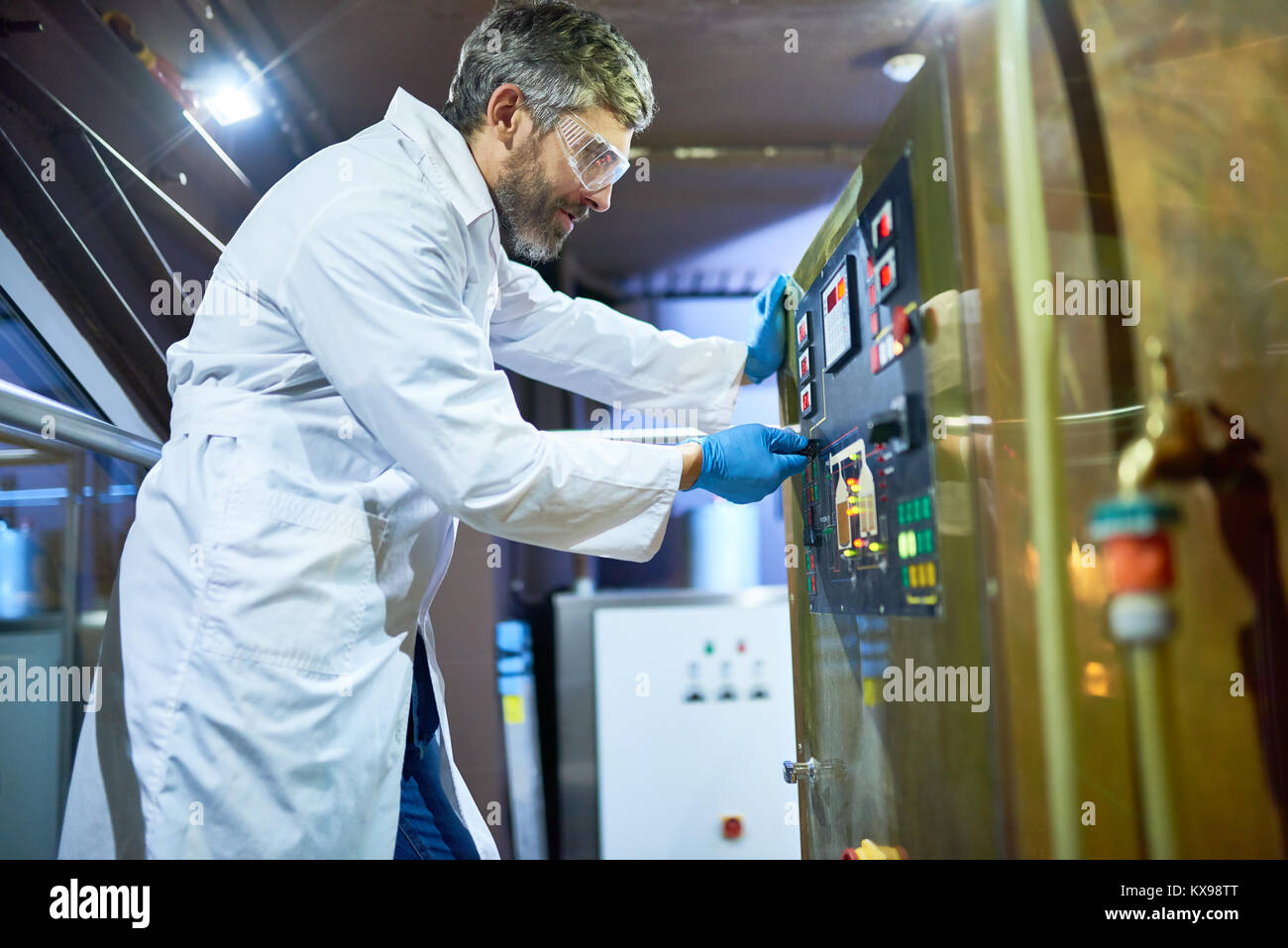Machine Operator Working at Modern Brewery - Stock Image