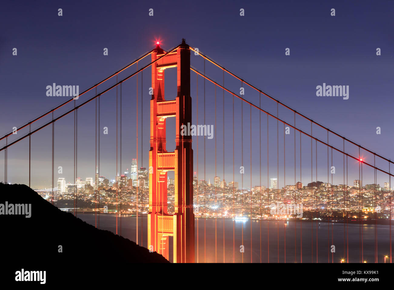 Golden Gate Bridge Close-up with San Francisco Skyline Background on a clear winter night. - Stock Image