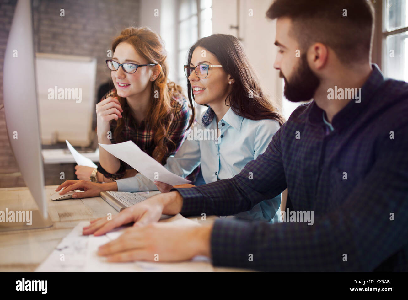 Group of young designers working as team - Stock Image