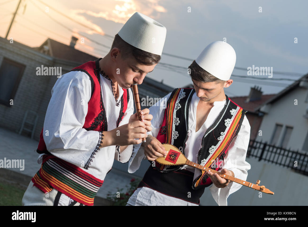 teen boys in traditional albanian costume playing music with flute and string instrument in the evening sunlight - Stock Image