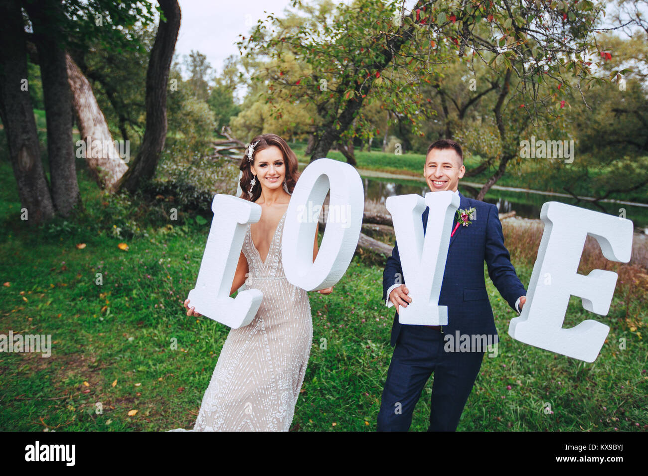 Happy Wedding Couple Holding Big White Love Letters And Kissing