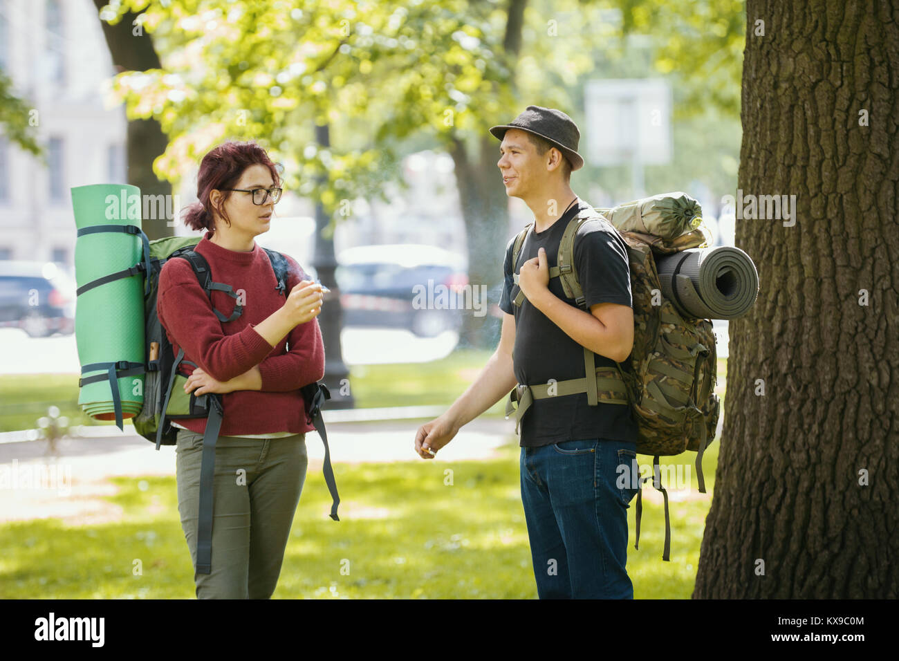 Teenagers tourists with backpacks - smoking and standing in the park at summer midday - Stock Image