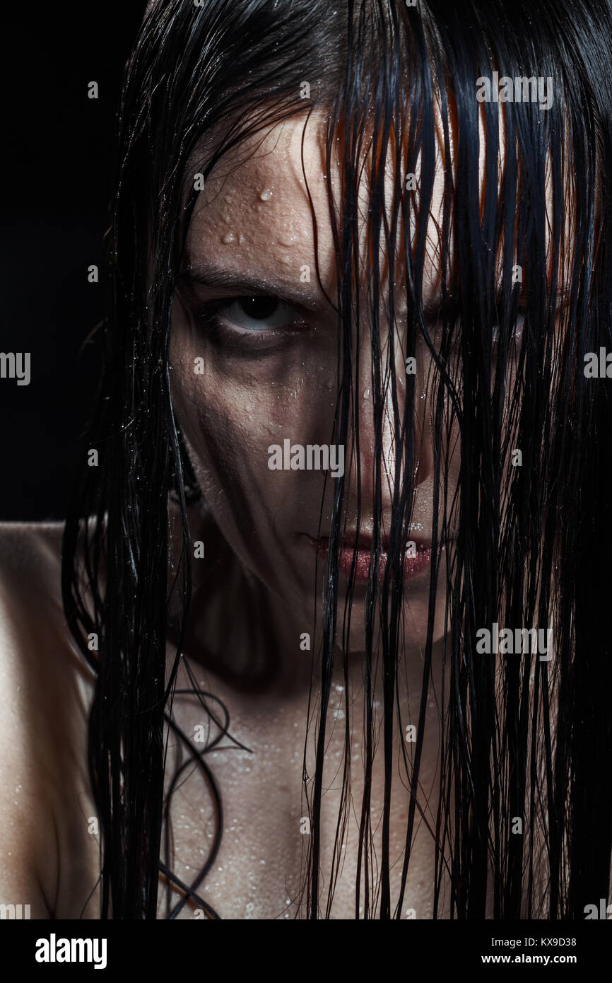 serious angry woman with wet black hair looking at camera - Stock Image