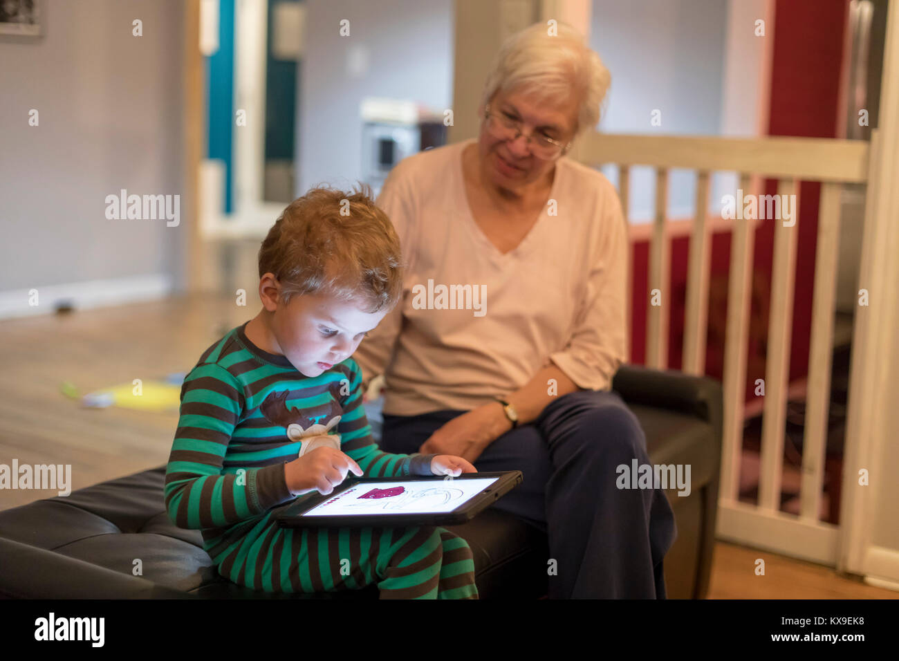 Wheat Ridge, Colorado - Susan Newell, 69, watches as her grandson, Adam Hjermstad Jr., 3, plays an educational game - Stock Image