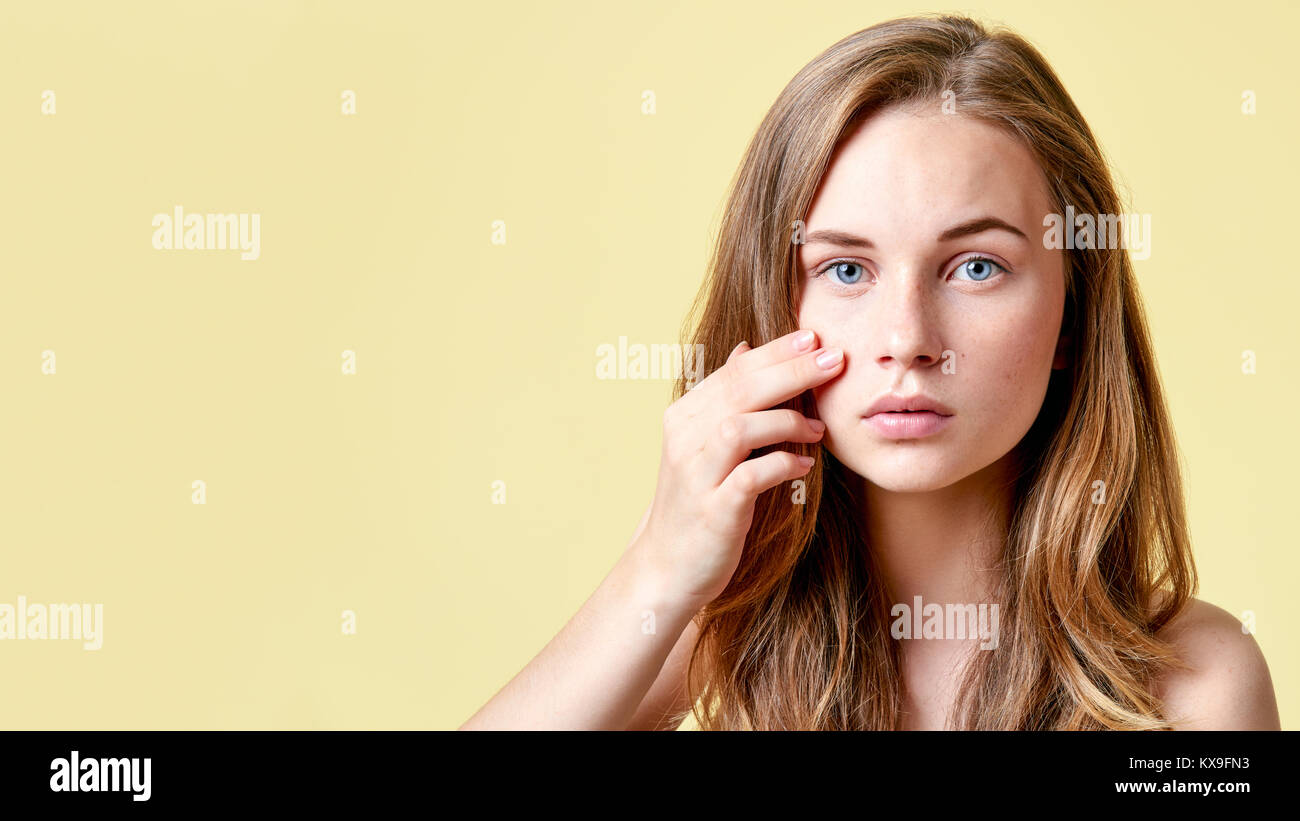 Young redhead teenager with self issues looking into mirror. Girl with low self esteem checking her skin in a mirror. - Stock Image