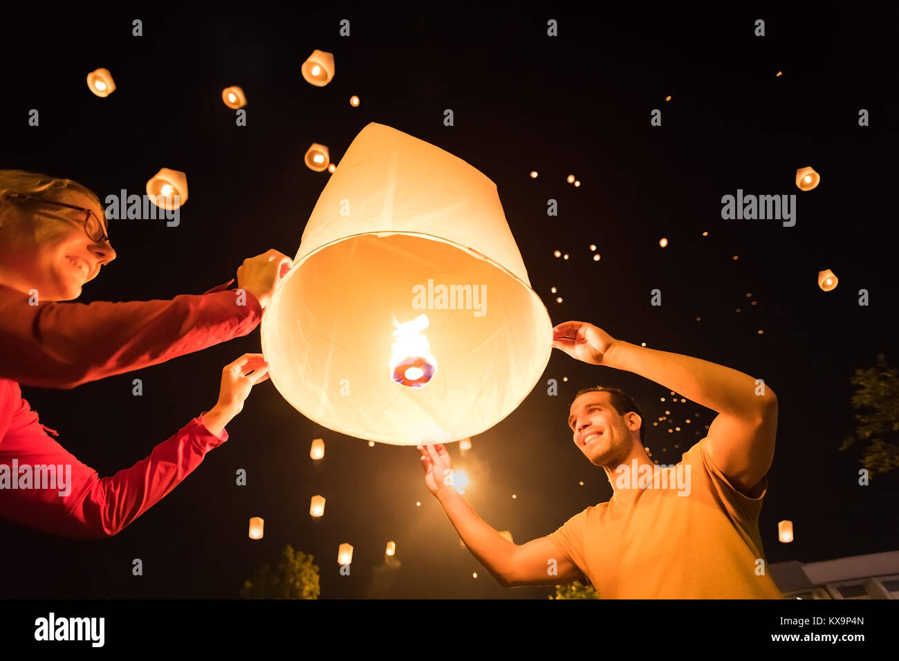 Two people releasing a traditional flying lantern at Yi Peng / Loy Krathong festival in Chiang Mai, Thailand Stock Photo