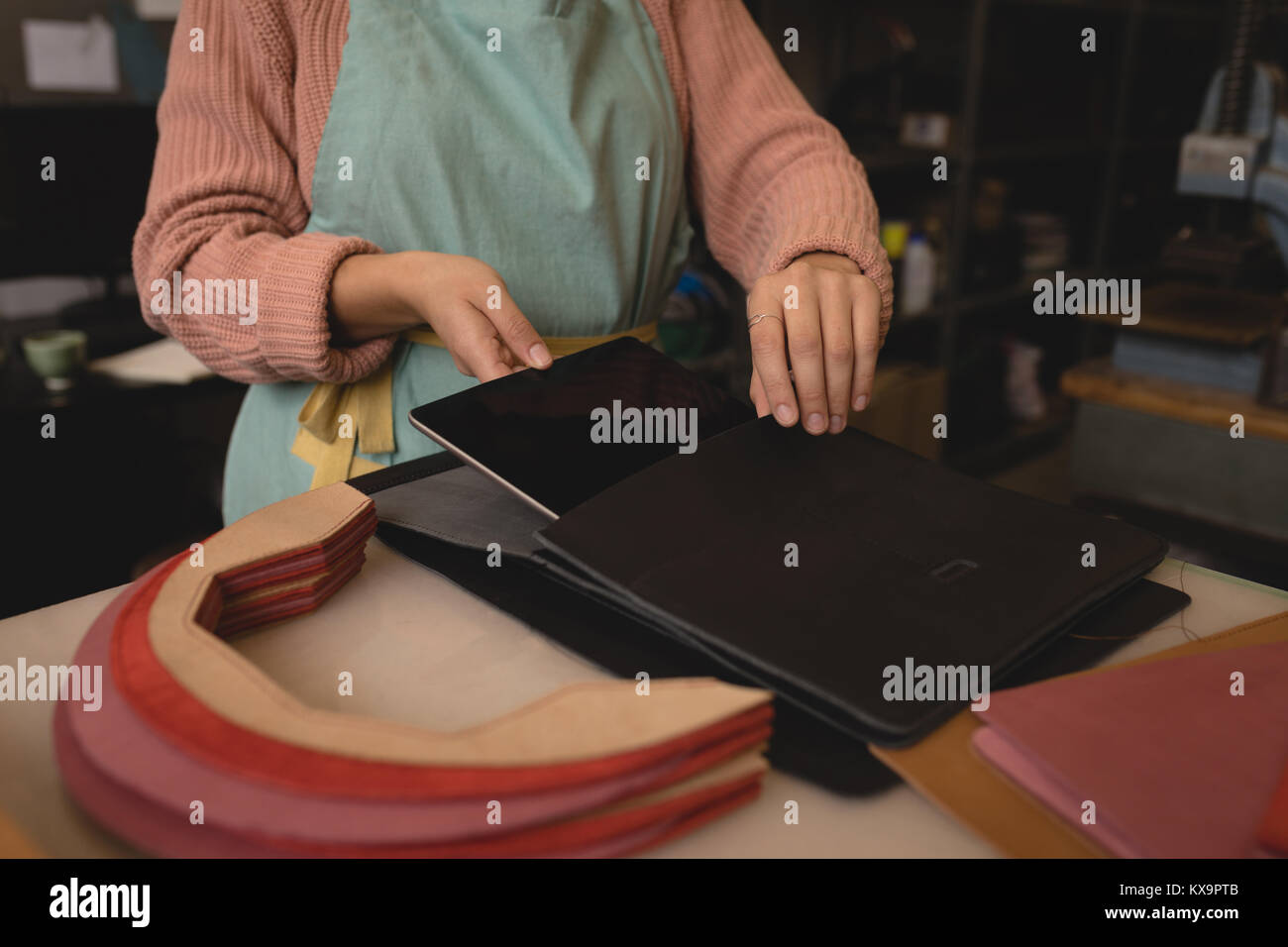 Female worker keeping digital tablet on leather pouch - Stock Image