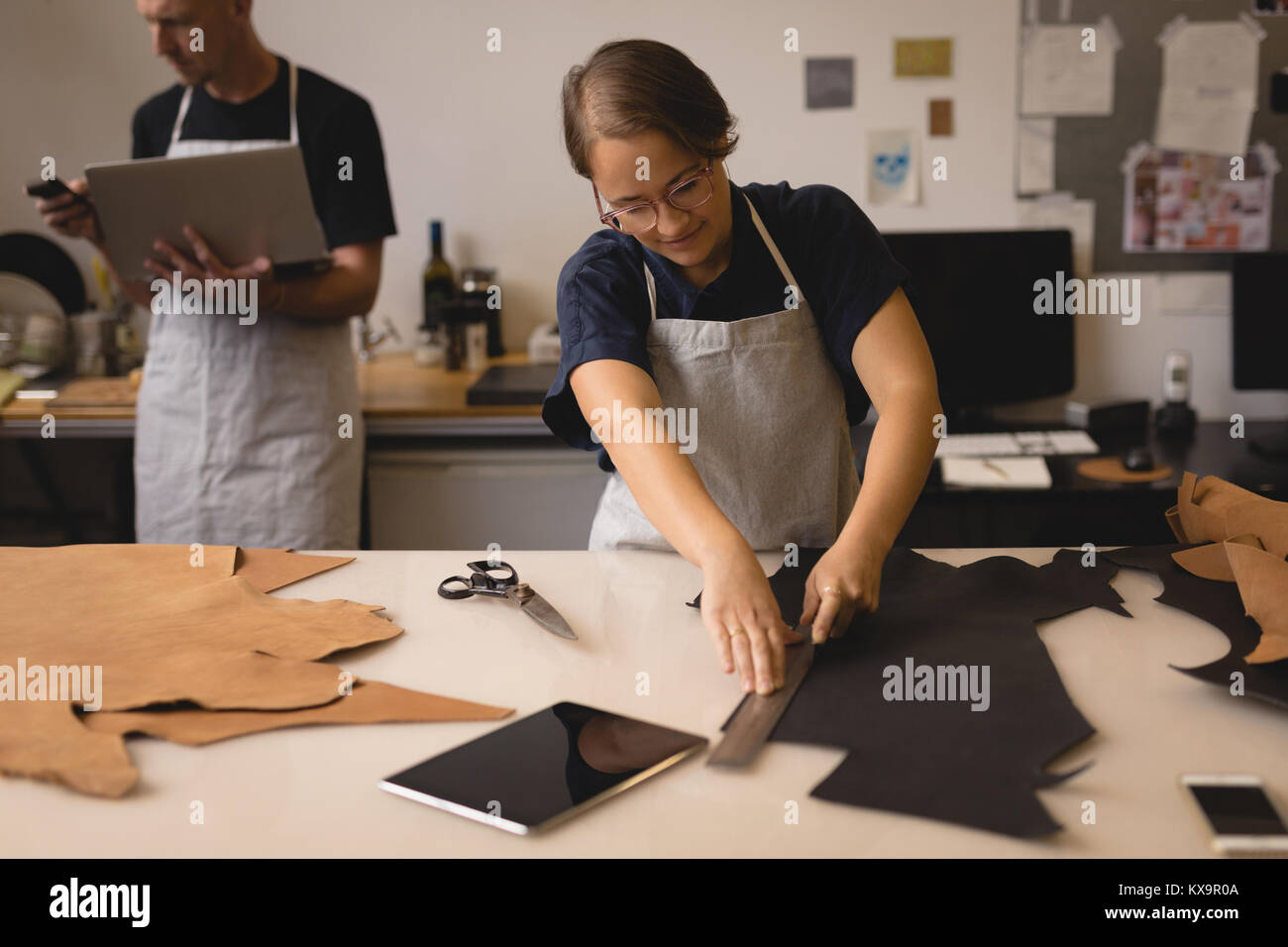 Worker measuring leather with ruler in workshop - Stock Image