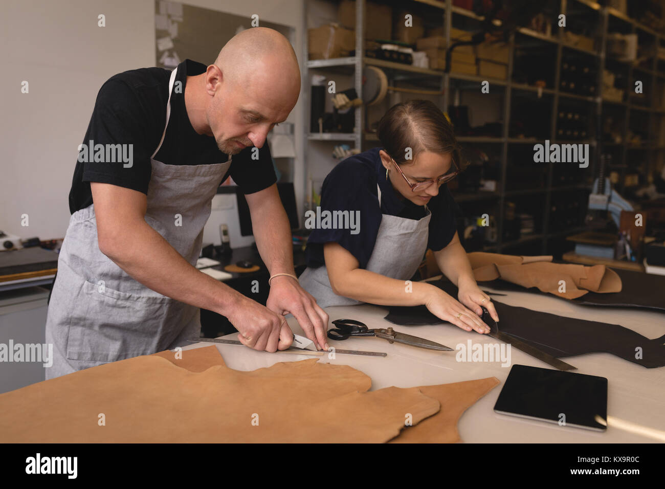 Workers measuring leather with ruler - Stock Image