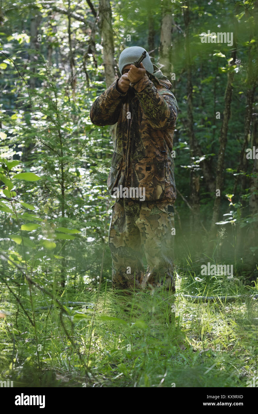 Hunter shooting with rifle in forest - Stock Image