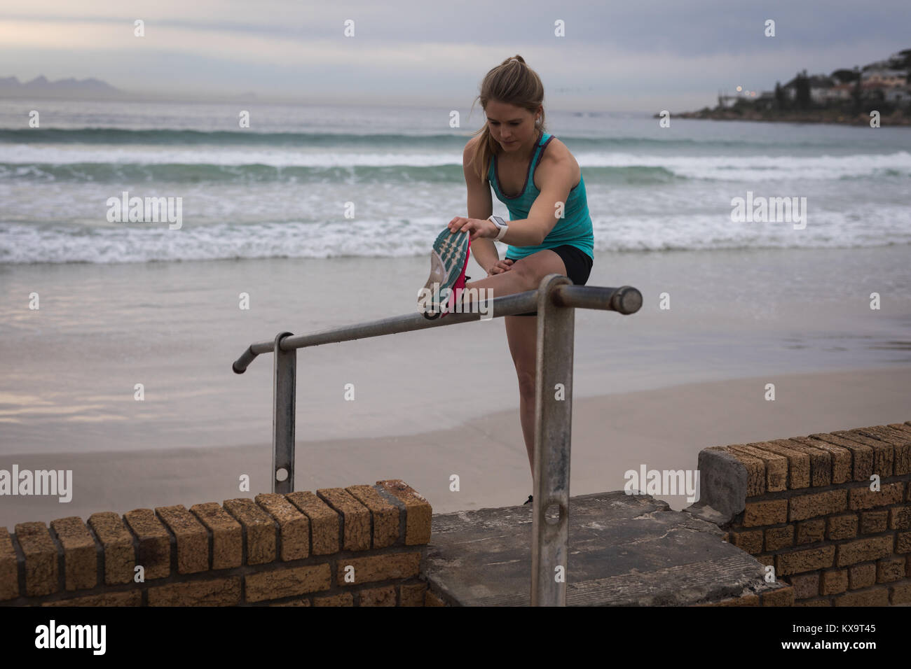 Woman performing stretching exercise near beach Stock Photo