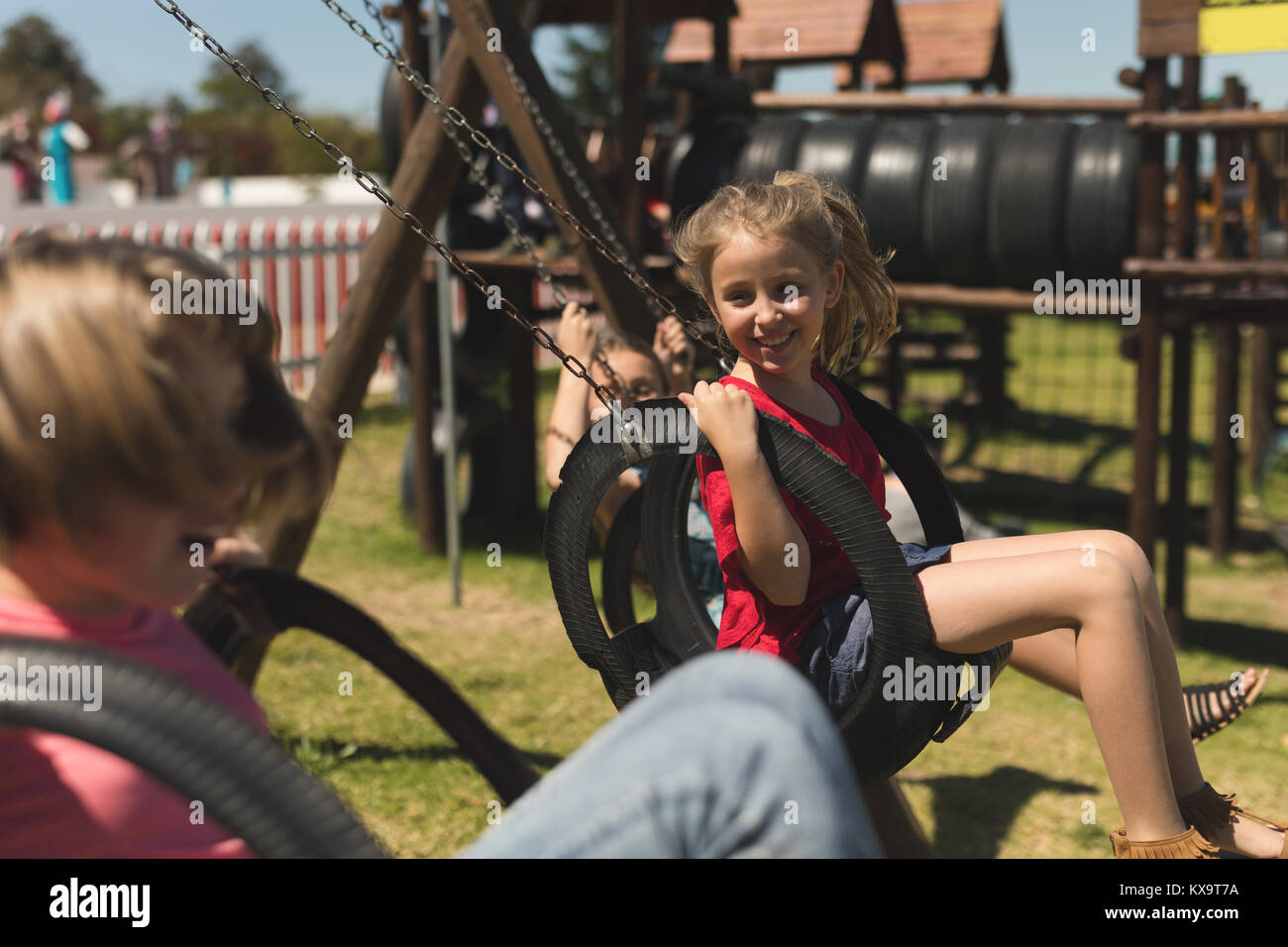 Children swinging on tire swing - Stock Image