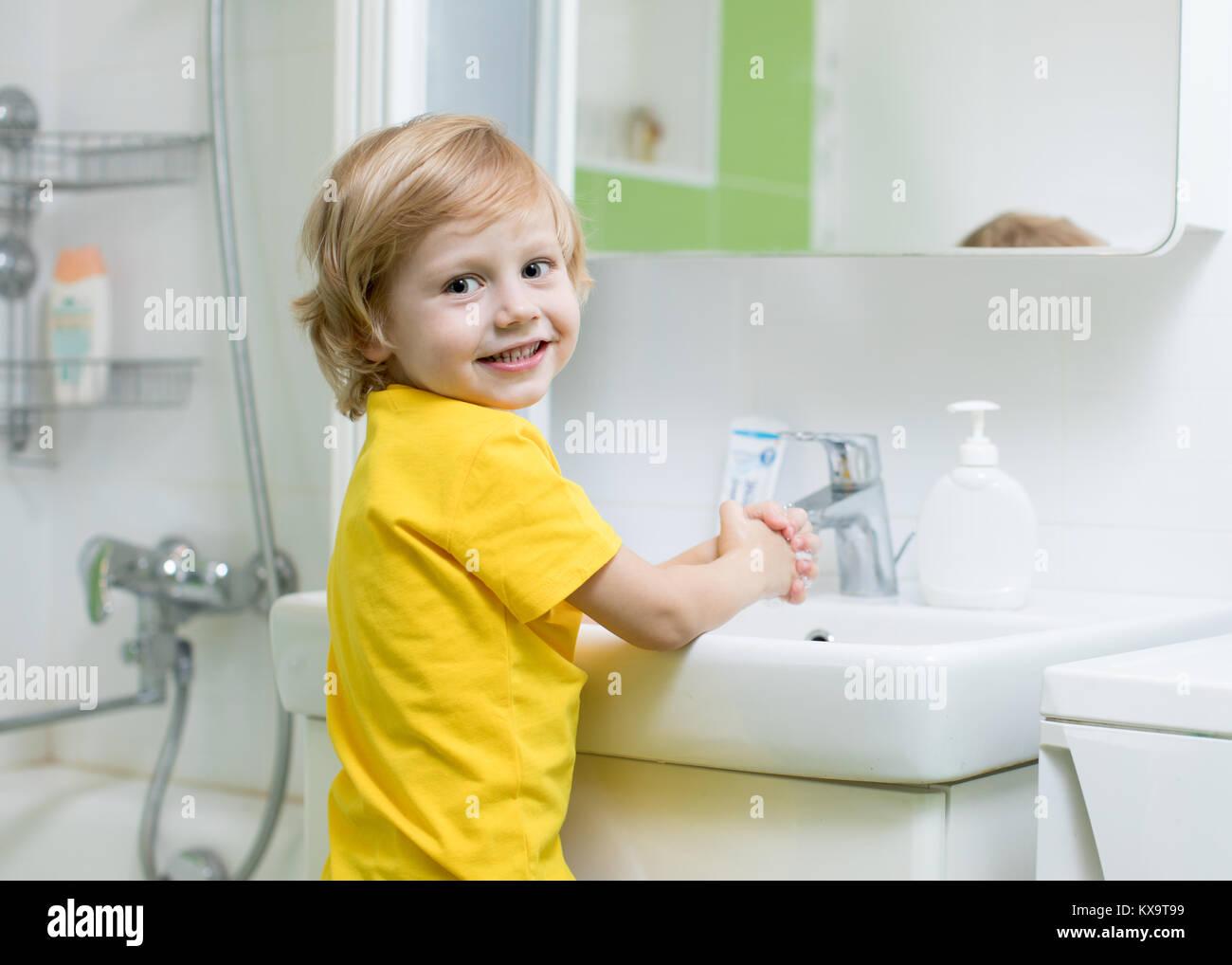 Little child boy washing hands in bathroom - Stock Image