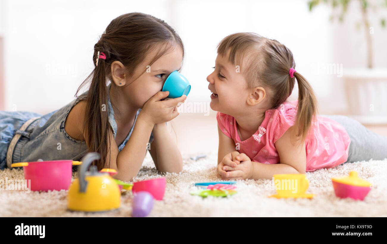 Cute funny children playing with toys on floor at home - Stock Image