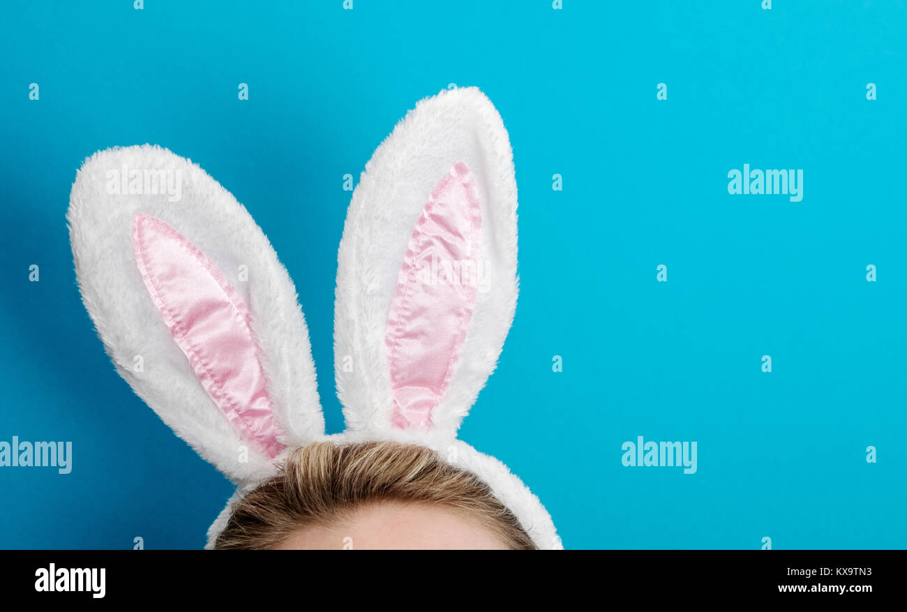 Easter bunny ears. Female wearing white bunny ears costume against a bright blue background Stock Photo