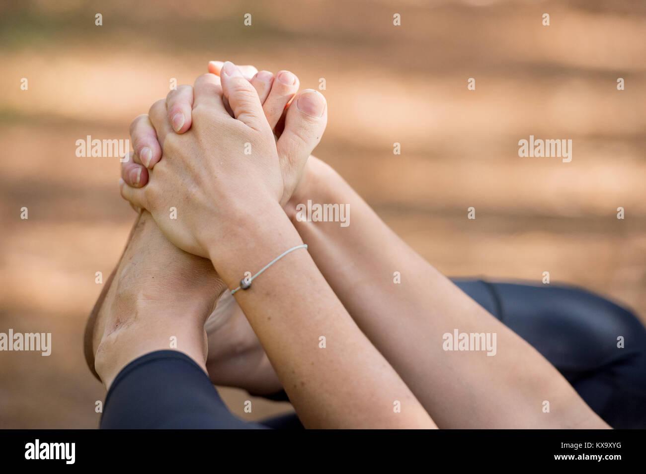 Woman practicing yoga in the sand - Happy Baby Pose - Ananda Balasana - Autumn day - Stock Image