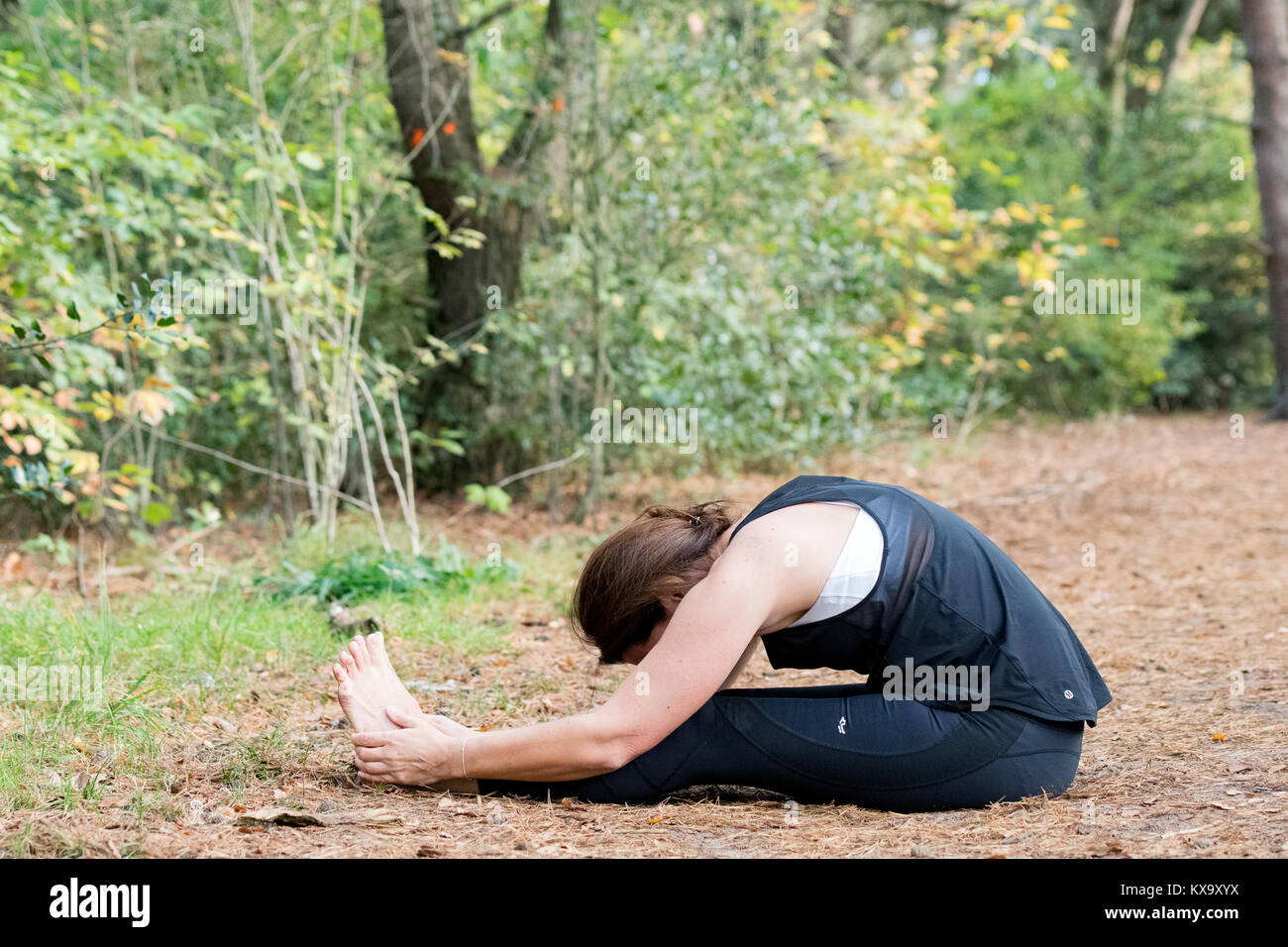 'Woman practicing yoga in the sand - Seated forward bend - Paschimottanasana - Autumn day' - Stock Image