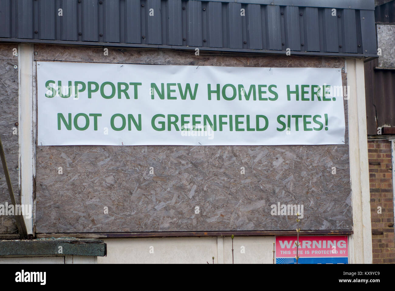 Support new homes here, not on greenfield sites protest banner on derelict building - Stock Image